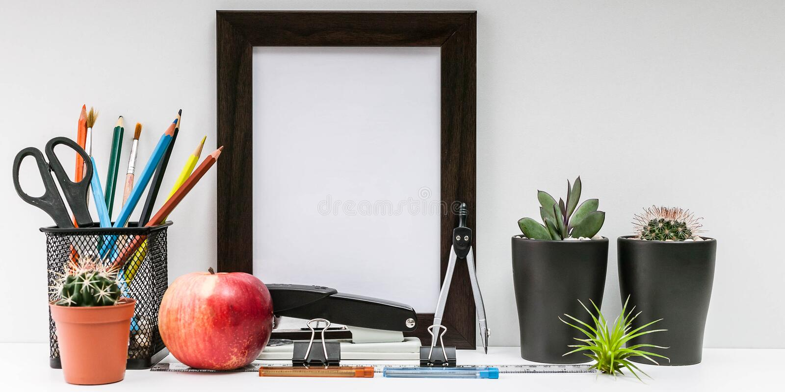 Empty dark photo frame, succulents in dark pots, colored pencils, office supplies, red apple on a white background. Desktop MockUp. Desktop MockUp. Scandinavian stock image