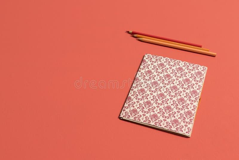 Desktop no caderno coral v?vido com teste padr?o do renascimento no fundo coral vivo foto de stock