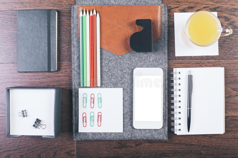Desktop with organized items. Top view of wooden tabletop with neatly organized office tools, orange juice and smartphone. Mock up royalty free stock image