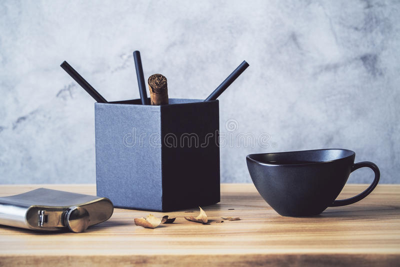 Desktop with pencil holder. Desktop with black pencil holder, coffee cup and flask on concrete wall background royalty free stock photos