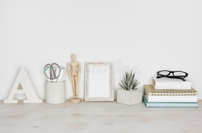 Desktop with picture frame, books, flower pot and educational supplies stock images