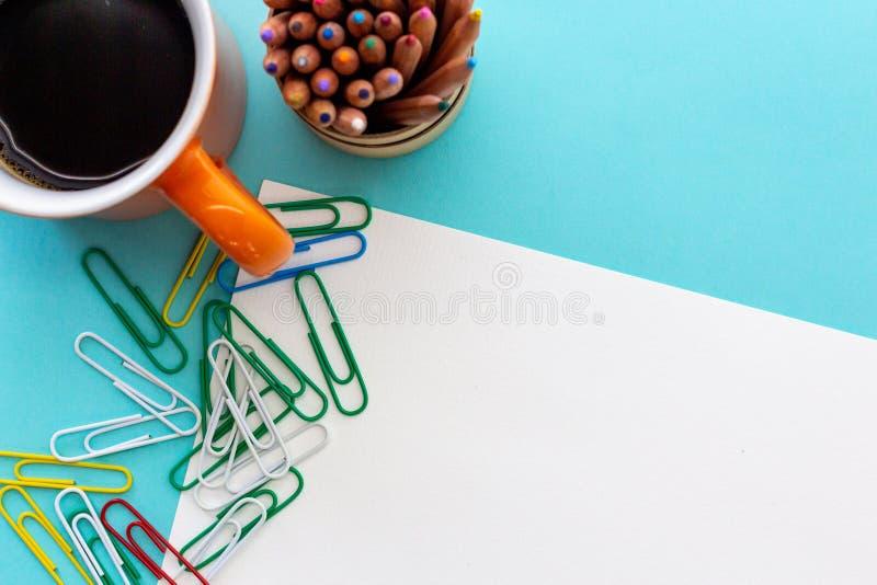 Desktop projekt z pomarańczowym kubkiem kawa, kolorowi paperclips i barwioni ołówki, zdjęcie royalty free