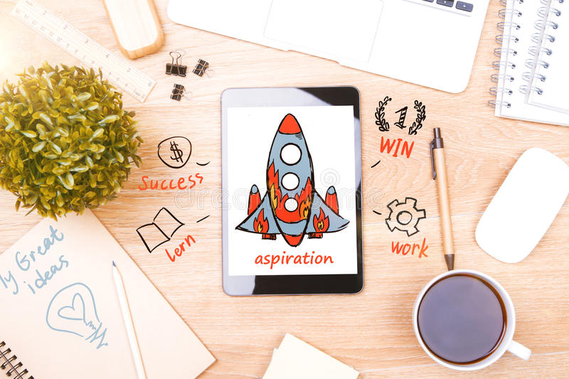 Desktop with rocket ship on smartphone screen. Top view of wooden desktop with rocket ship on smartphone screen. Aspirations concept royalty free stock photography