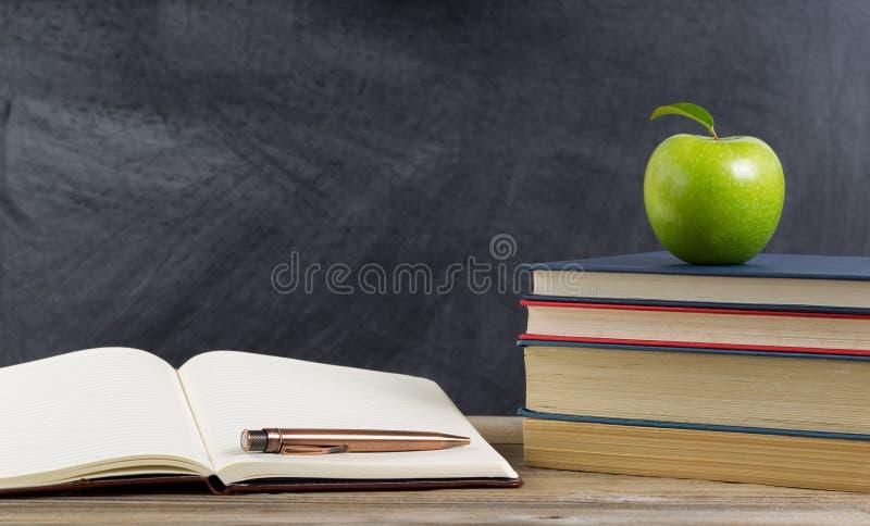 Desktop rustico dello studente con i materiali verdi di studio e della mela immagini stock libere da diritti