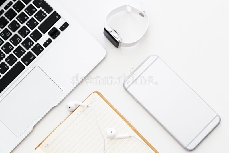 Desktop rzeczy: laptop, notatnik, he?mofony, telefon kom?rkowy, m?drze zegarka lying on the beach na bia?ym tle Mieszkanie nieatu obraz royalty free
