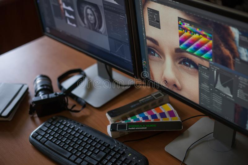 Desktop with two monitors, a keyboard, a camera, a diary, a palette for a designer, a retoucher, a photographer. With the image of the model on the monitors in royalty free stock photo