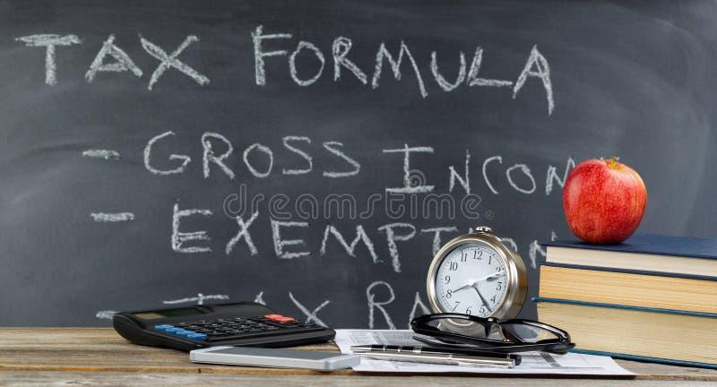 Desktop und Tafel für das Lernen, wie man Einkommenssteuern im Cl tut lizenzfreie stockfotografie