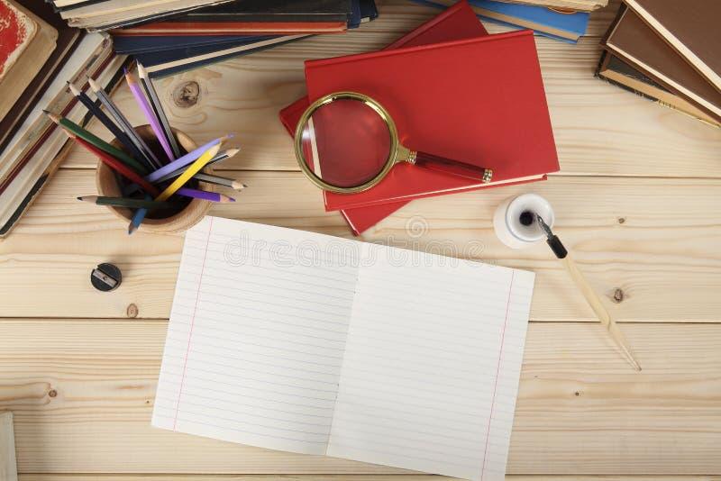 desktop Visión desde arriba Vidrio de la lupa, lápices coloreados en una taza de madera, cuaderno, pluma retra con la pluma y tin imagen de archivo libre de regalías