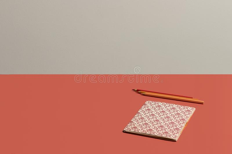 Desktop in vivid coral notebook with Renaissance pattern in live coral background royalty free stock image