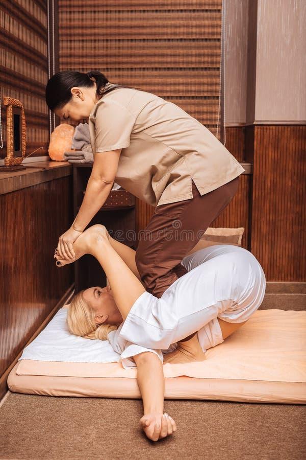 Deskundige aardige Aziatische masseuse die Thaise massage doen royalty-vrije stock foto's