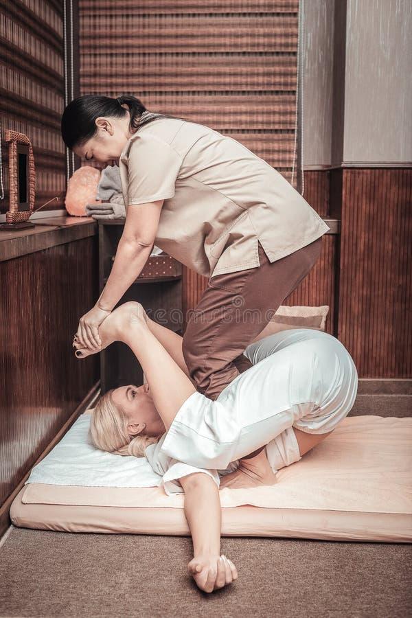 Deskundige aardige Aziatische masseuse die Thaise massage doen stock afbeeldingen
