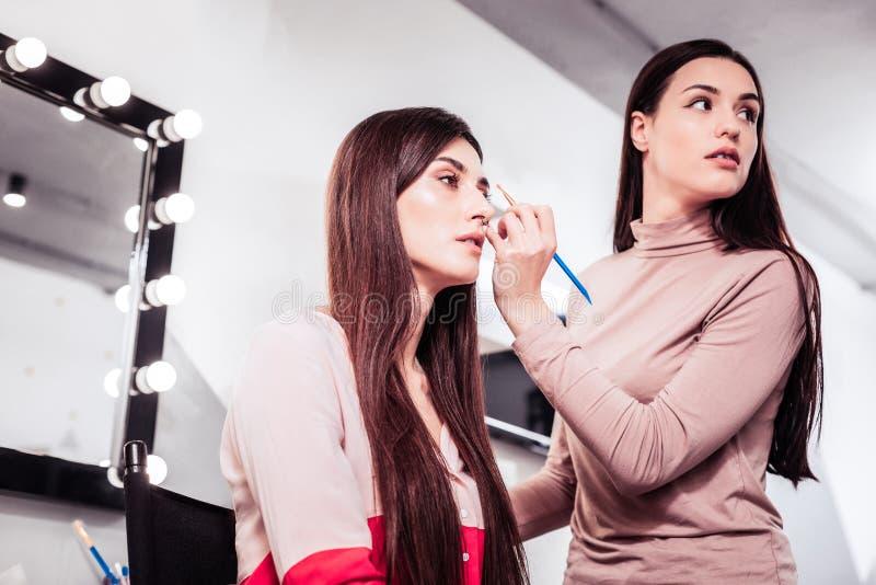 Deskundige de make-upkunstenaar die van Nice de spiegel onderzoeken royalty-vrije stock foto's
