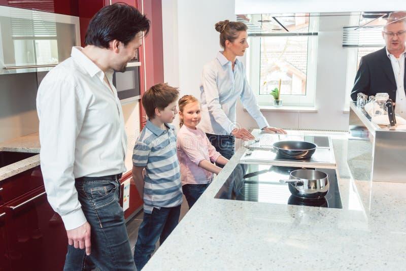 Deskundige die nieuwe keuken verklaren aan familie die zoeken stock foto's