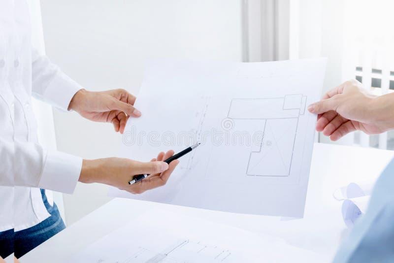 Deskundige ingenieurs/bedrijfsmensen die een bouwconstructieproject bespreken op het werk stock foto's
