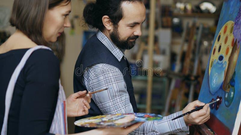 Deskundige kunstenaarsleraar die en grondbeginselen van het schilderen tonen bespreken aan student bij kunst-klasse stock afbeelding
