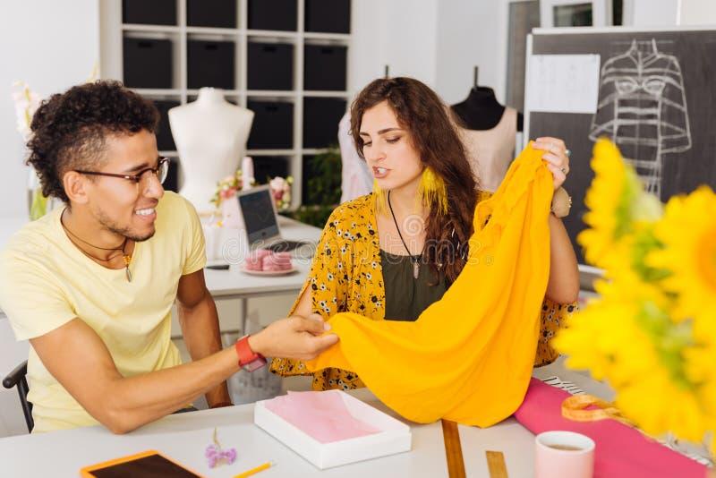 Deskundige naaisters die de textiel bespreken terwijl wat betreft gele blouse stock foto's