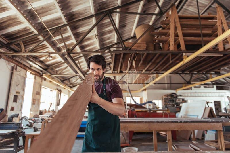 Deskundige schrijnwerker die een houten plank in zijn workshop onderzoeken royalty-vrije stock afbeeldingen