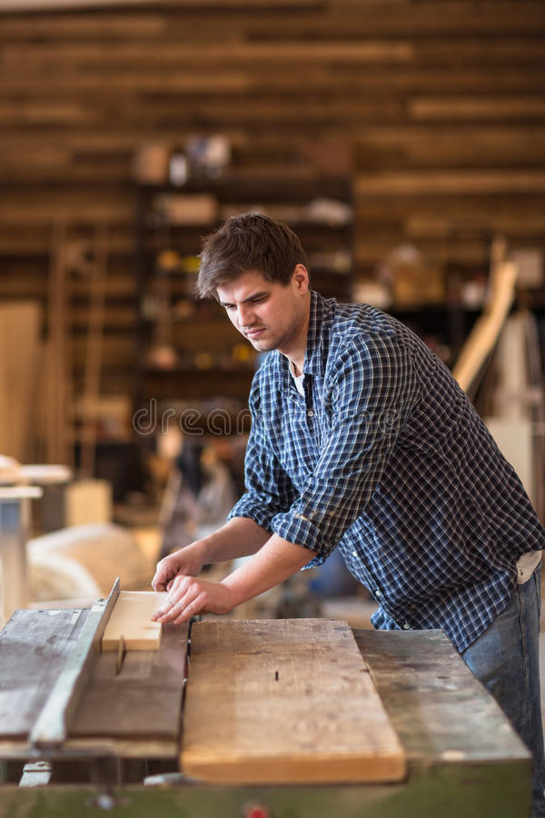 Deskundige timmerman die in zijn houtbewerkingsworkshop werken, die een circ gebruiken stock afbeelding