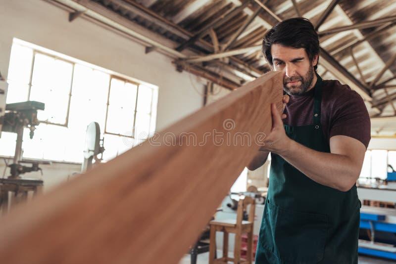 Deskundige vakman die een plank van hout in zijn workshop onderzoeken royalty-vrije stock fotografie