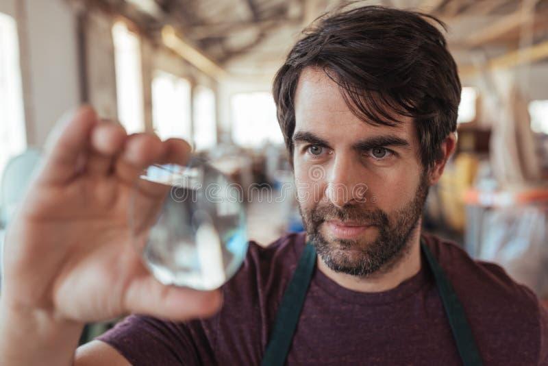 Deskundige vakman die een stuk van glas in zijn workshop onderzoeken stock fotografie