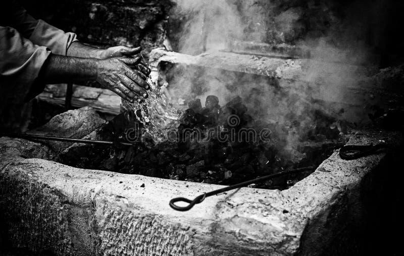 Desligar arde com água no carvão fotos de stock royalty free