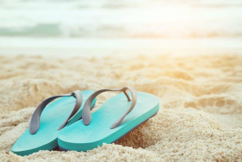 Deslizador do pé em sapatas das sandálias e da distribuição de água azul da onda de oceano em arenoso imagem de stock
