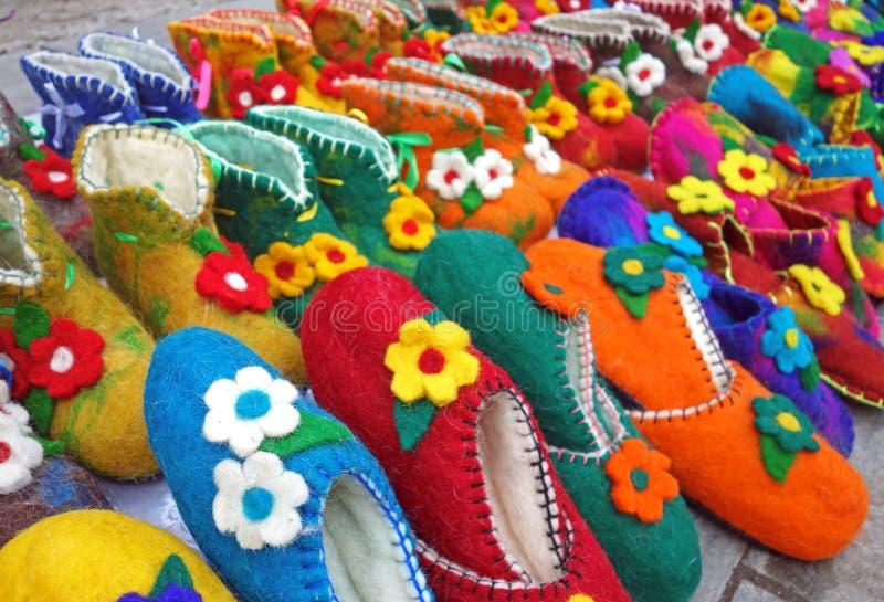 Deslizadores o zapatos coloridos hechos a mano de las lanas para la venta en la calle fotos de archivo