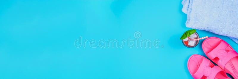 Deslizadores, uma toalha e um cocktail do gelo em um fundo pastel azul Resto, curso Vista superior Copie o espaço Configuração li imagem de stock royalty free