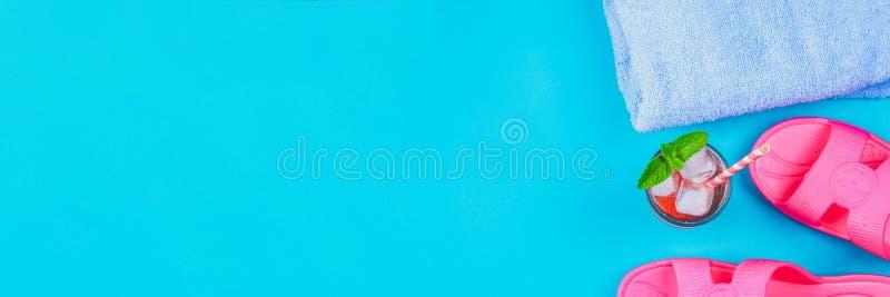 Deslizadores, uma toalha e um cocktail do gelo em um fundo pastel azul Resto, curso Vista superior Copie o espaço Configuração li imagens de stock royalty free
