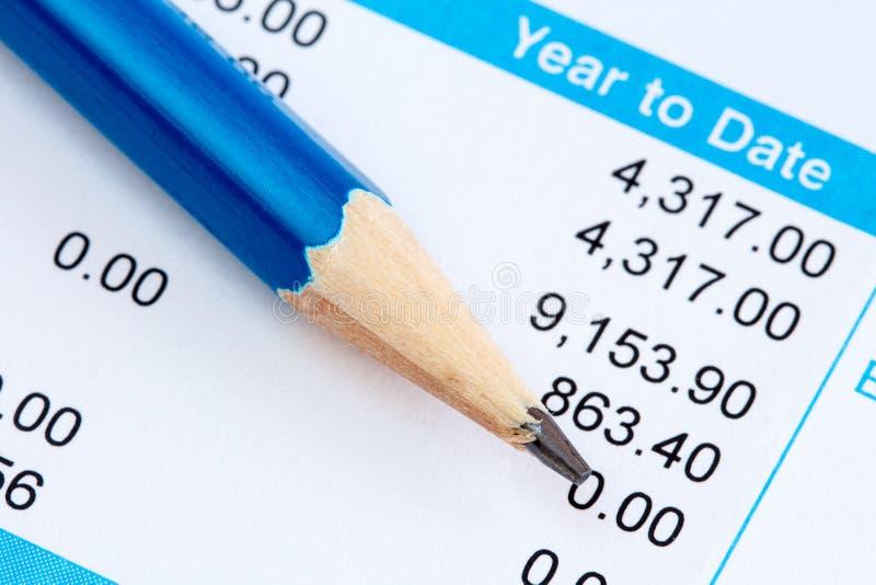 Deslizamento do lápis e do salário foto de stock