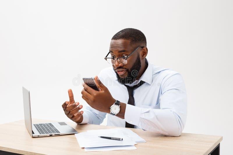 Deslumbran al hombre de negocios africano decepcionado y el hablar confundido en el teléfono Él siente el desacuerdo total sobre  foto de archivo