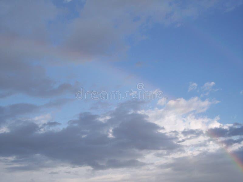 Desmaia o arco-íris dobro contra o céu azul e as nuvens imagem de stock royalty free