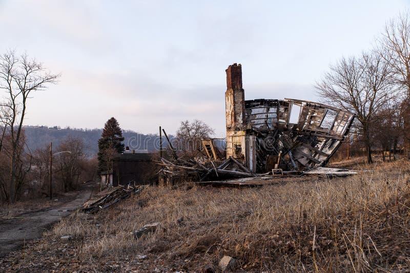 Desmoronando, casa abandonada na rua estéril no por do sol foto de stock