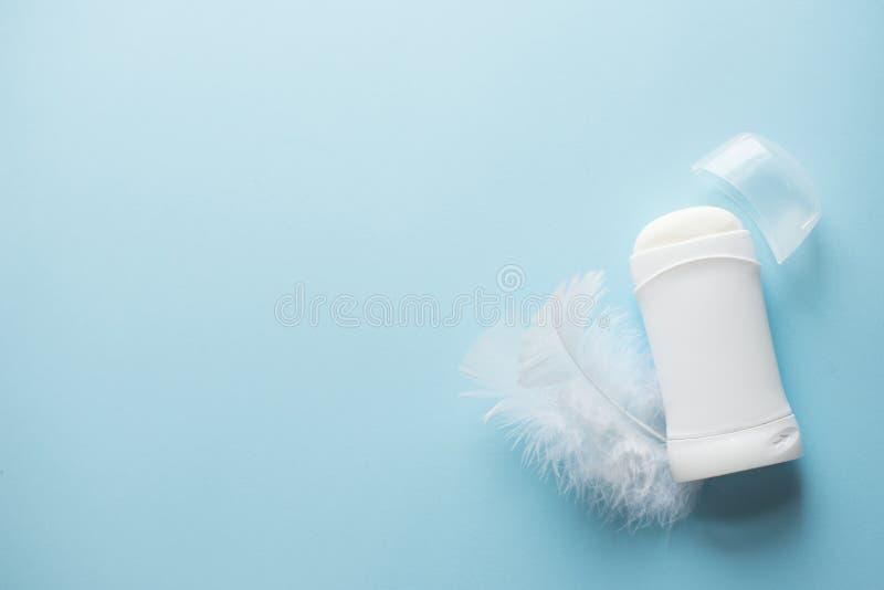 Desodorante antitranspirante en fondo azul con las plumas blancas Copie el espacio, visi?n superior Cuidado de piel del cuerpo foto de archivo