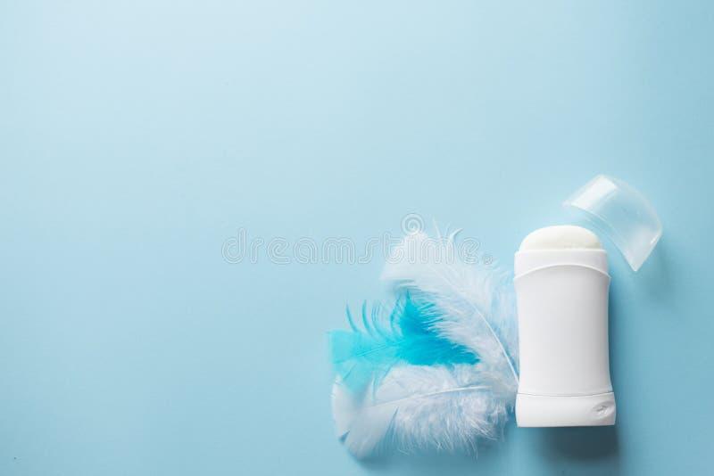 Desodorante o desodorante blanco con las plumas en el fondo azul para el concepto del cuidado de piel del cuerpo Copie el espacio imagen de archivo