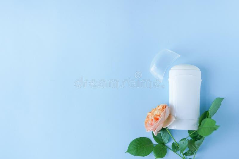 Desodorierendes Mittel und Blumen auf blauem Hintergrund mit Kopienraum flache gelegte Körperpflege stockbild