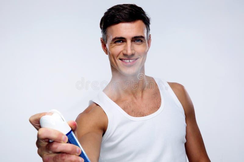 Desodorizante de pulverização feliz do homem fotografia de stock royalty free
