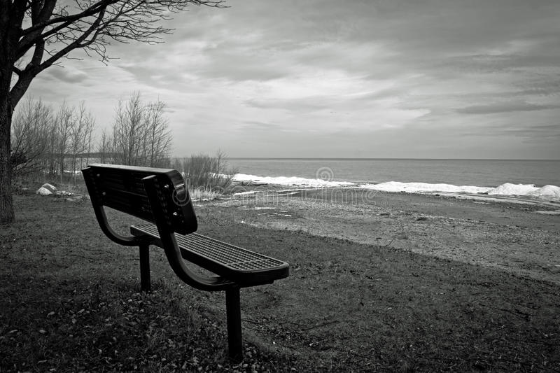 Desolate. Black and white photo of a vacant bench on a desolate Lake Michigan beach royalty free stock images