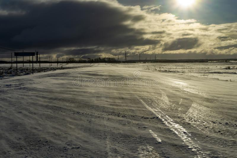Desolate empty, icy road and harsh sunlight. A desolate empty, icy road lit by harsh sunlight, leading to silhouetted industrial buildings stock image