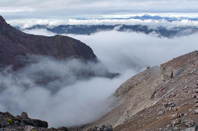 Desolate landscape on Cayambe Volcano. With a cloud filled valley beyond, Ecuador stock images