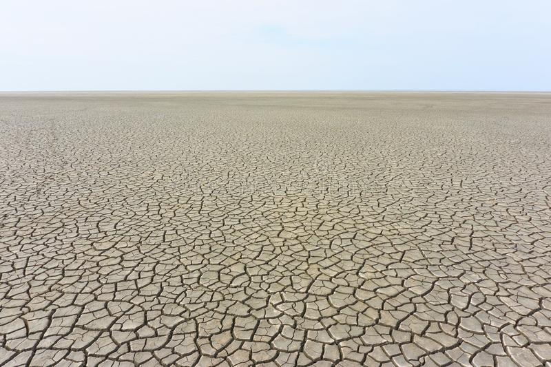 Desolate landscape with cracked ground. At the seashore. Brown, beige, light tan and grey colored. Concept of global warming royalty free stock photography