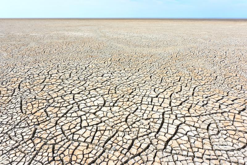 Desolate landscape with cracked ground at the seashore. Brown, beige, light tan and grey colored. Concept of global warming royalty free stock photography