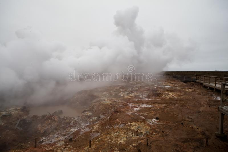 Desolate landscape of Iceland volcanic brown soil with steamy geyser mist. And grey colored sky royalty free stock photos