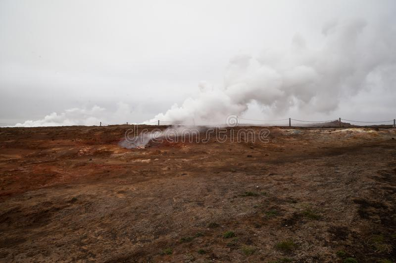 Desolate landscape of Iceland volcanic brown soil with steamy geyser mist. And grey colored sky stock photo