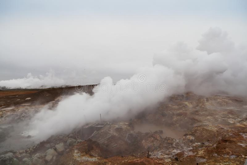 Desolate landscape of Iceland volcanic brown soil with steamy geyser mist. And grey colored sky royalty free stock photo