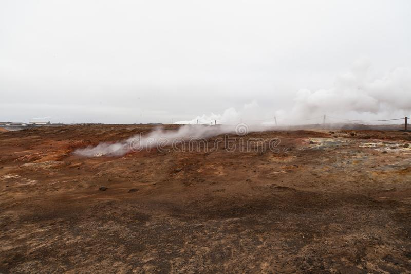 Desolate landscape of Iceland volcanic brown soil with steamy geyser mist. And grey colored sky royalty free stock images