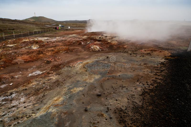 Keflavik Geothermal Area, Iceland - June 2018: Desolate landscape of Iceland volcanic soil with steamy mist and tourists. Desolate landscape of Iceland volcanic stock photo