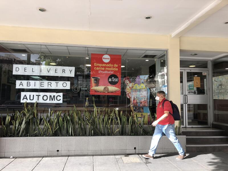 Desolation. A man walks through Mac Donalds food store during lockdown amid Covid-19 pandemic royalty free stock image