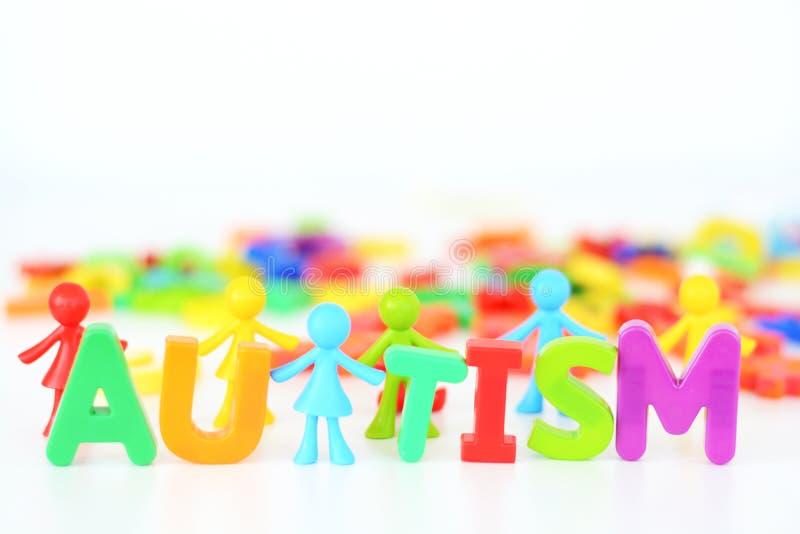Desorden de la salud mental, palabra del autismo con la estatuilla coloreada de los juguetes en el fondo blanco imagen de archivo libre de regalías
