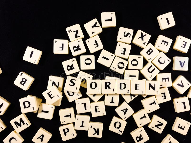 Desorden word spelled with letter tiles in black background stock photos